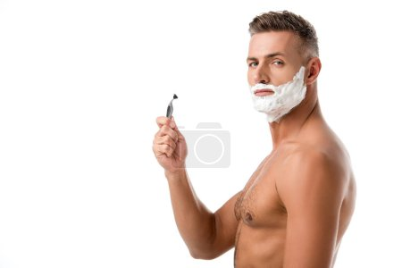 muscular shirtless man with shaving foam on face holding razor isolated on white