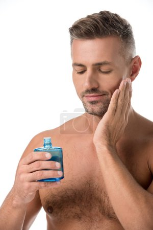 adult handsome man using shaving lotion isolated on white