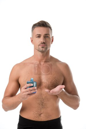 man with muscular torso pointing at shaving lotion isolated on white
