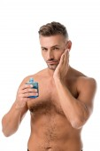 confident shirtless muscular man using shaving lotion isolated on white