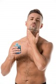 shirtless muscular man using shaving lotion isolated on white