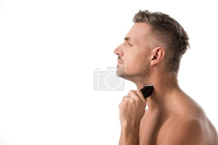 side view of handsome adult man shaving with electric trimmer isolated on white