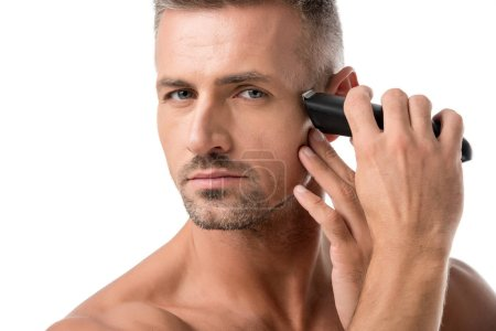 portrait of adult man shaving with electric trimmer isolated on white