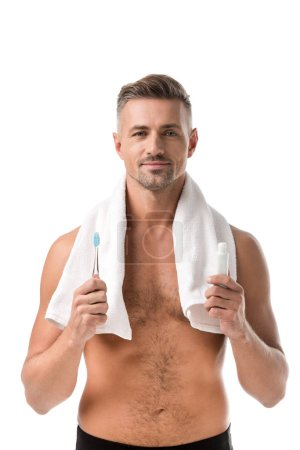 happy adult man with towel over neck holding toothbrush and toothpaste isolated on white