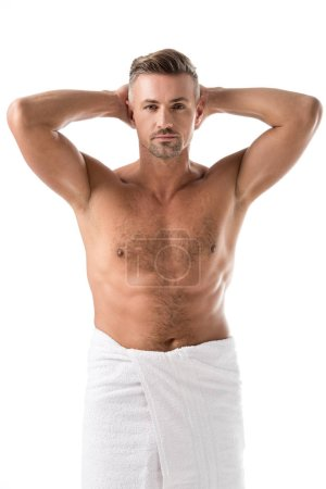 adult muscular shirtless man wrapped in towel posing with raised arms isolated on white