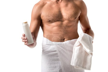 cropped image of muscular shirtless man wrapped in towel holding shower gel isolated on white