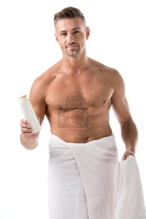 happy adult man wrapped in towel holding shower gel isolated on white