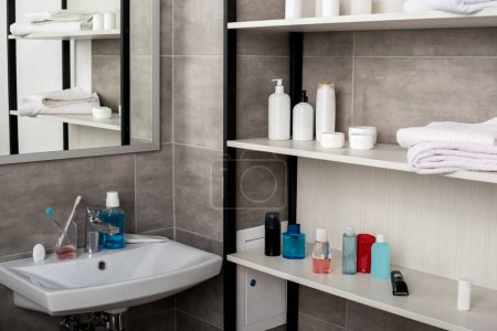 selective focus of modern bathroom with sinks and shelves with beauty products