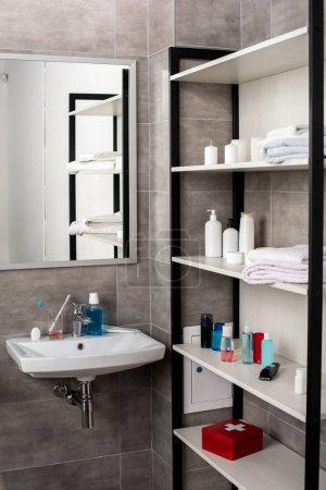 Photo pour Intérieur de la salle de bains moderne avec puits et les étagères avec des produits de beauté - image libre de droit