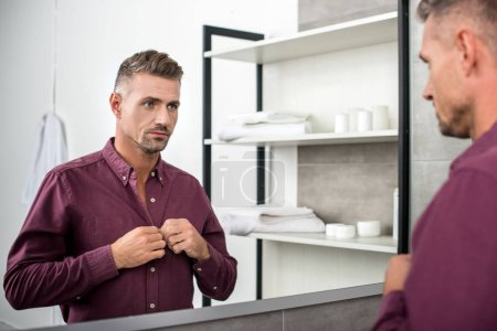 adult businessman looking at mirror and buttoning up shirt in bathroom at home