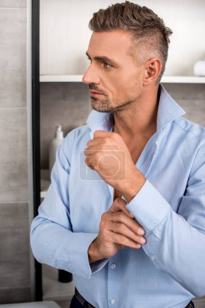 handsome adult businessman buttoning up blue shirt in bathroom at home