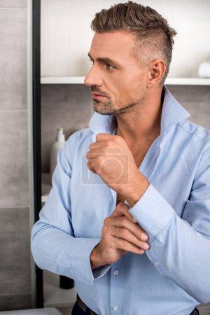 Photo pour Bel homme d'affaires adulte boutonnant chemise bleue dans la salle de bain à la maison - image libre de droit