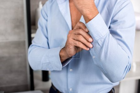cropped image of businessman buttoning up blue shirt in bathroom at home