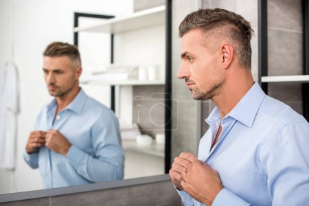 selective focus of adult businessman buttoning up blue shirt in bathroom at home