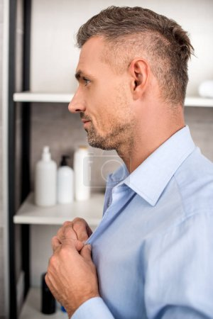 side view of adult businessman buttoning up blue shirt in bathroom at home