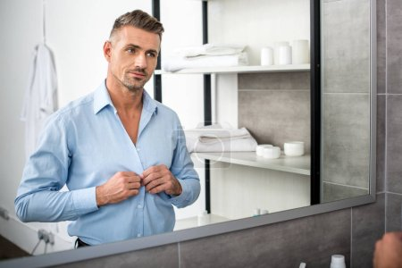 adult businessman looking at mirror and buttoning up blue shirt in bathroom at home
