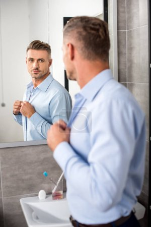 rear view of adult businessman looking at mirror while buttoning up blue shirt in bathroom at home