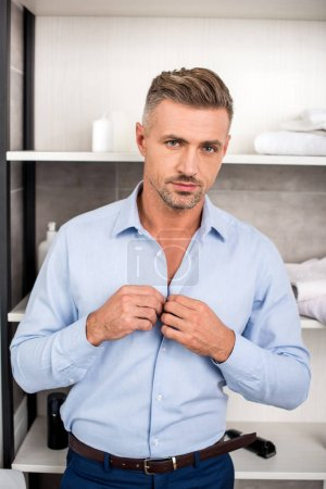 portrait of adult businessman looking at camera and buttoning up blue shirt in bathroom at home