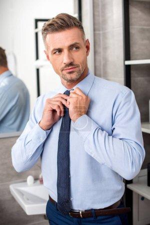 ernsthafte erwachsene Geschäftsmann binden Krawatte im Badezimmer
