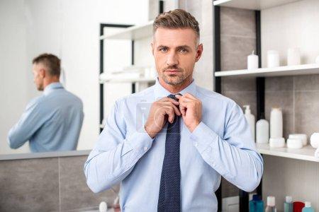 portrait of handsome businessman tying necktie in bathroom
