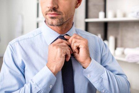 partial view of businessman tying necktie in bathroom