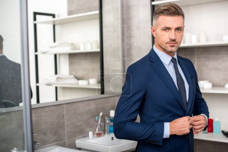 selective focus of adult businessman buttoning up suit jacket in bathroom