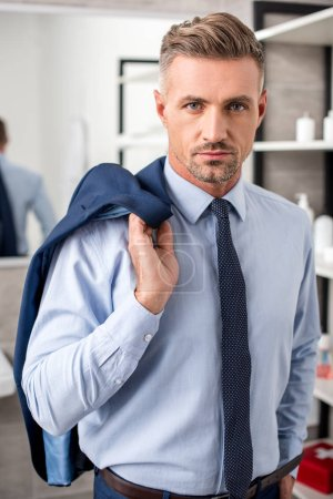 serious adult businessman posing with jacket over shoulder in bathroom