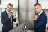 high angle view of adult businessman adjusting necktie in front of mirror in bathroom