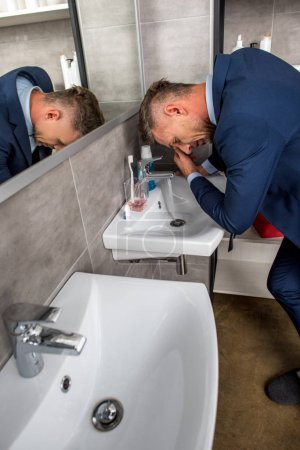 high angle view of businessman washing face over sink in bathroom