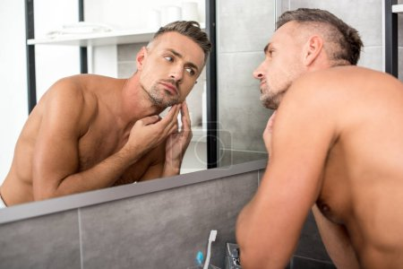confident shirtless adult man looking at mirror in bathroom