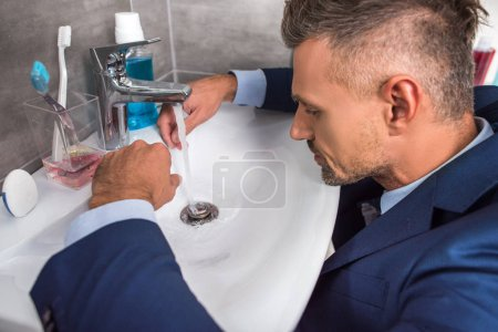 side view of adult businessman in suit sitting in front of sink in bathroom