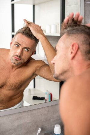 selective focus of adult man adjusting haircut and looking at mirror in bathroom