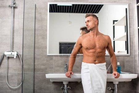 confident muscular shirtless man in towel posing near sinks in bathroom