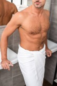 cropped image of shirtless muscular man in towel posing near sinks in bathroom
