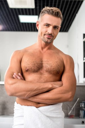 low angle view joyful muscular man with crossed arms posing near sinks in bathroom