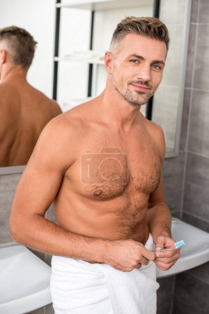 happy shirtless man with muscular torso standing with toothbrush and looking at camera in bathroom