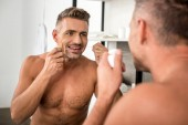 selective focus of handsome man using dental floss and looking at mirror in bathroom
