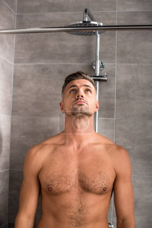 shirtless adult man with muscular torso standing under shower