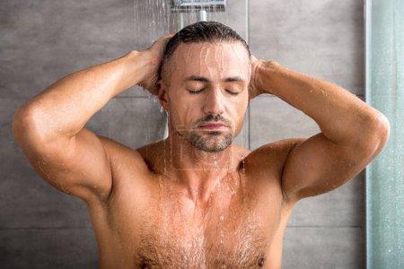Portrait d'un homme adulte avec les yeux fermés prendre douche matin