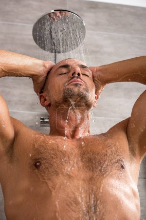 low angle view of adult man with muscular torso taking shower in morning