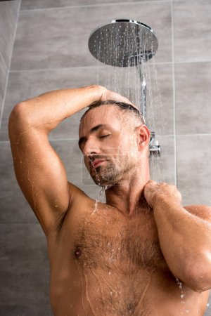 man with closed eyes taking shower in morning at home