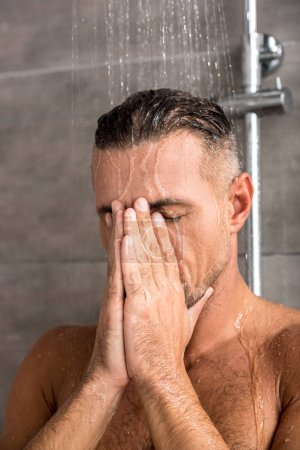 selective focus of adult man with hands on face taking shower in morning