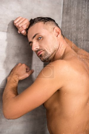 handsome man leaning on wall and looking at camera while taking shower in morning