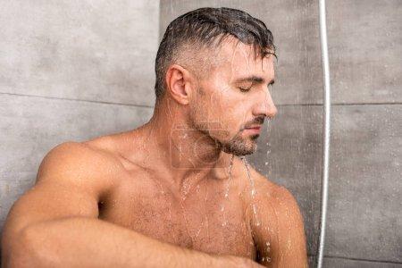 Photo pour Homme avec des yeux fermés, prendre la douche dans la matinée à la maison - image libre de droit
