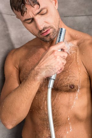 selective focus of adult handsome man taking shower in morning