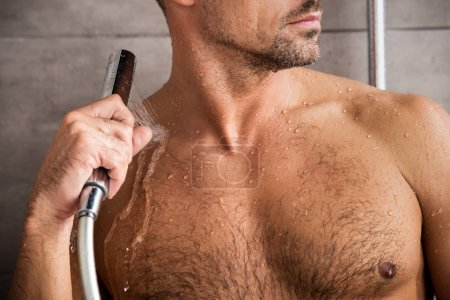 Photo pour Vue partielle de l'homme à prendre de douche dans la matinée à la maison - image libre de droit