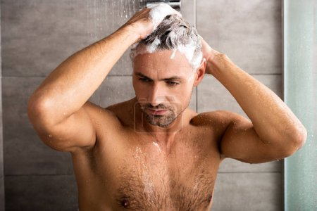 selective focus of adult man washing hair with shampoo and taking shower