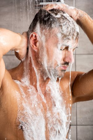 adult man with closed eyes washing foam in shower