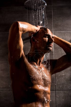 low angle view of adult man taking shower in morning