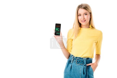 attractive young woman holding smartphone with marketing analysis app and smiling at camera isolated on white